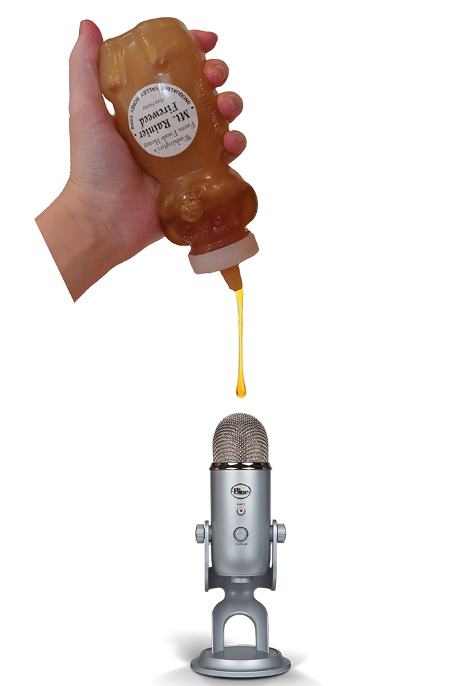 Photograph of a hand squeezing a plastic bear bottle of honey with the dangling trail of honey almost touching the tip of a silver microphone.