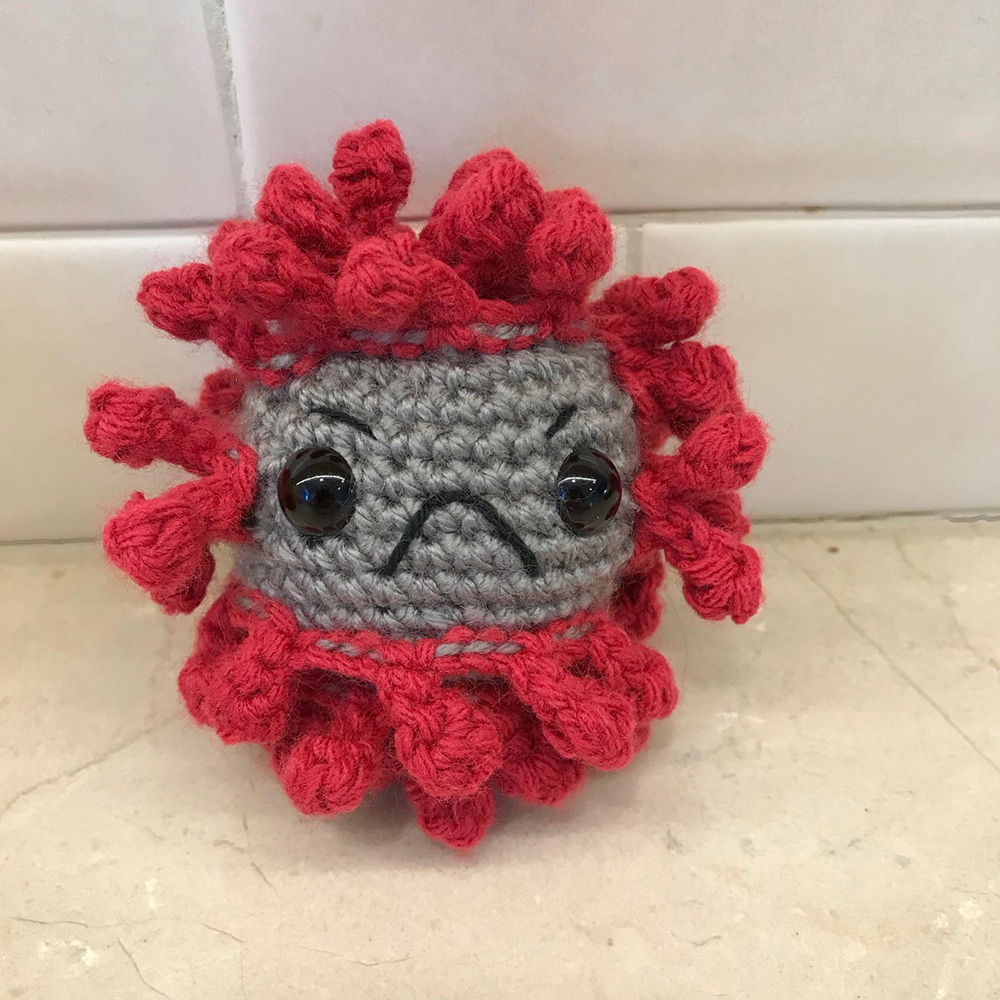A photograph of a small crocheted virus with a black frowny face.